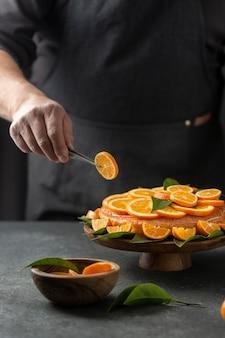 Chef-kok van het gebakje stukjes sinaasappel op de taart te zetten