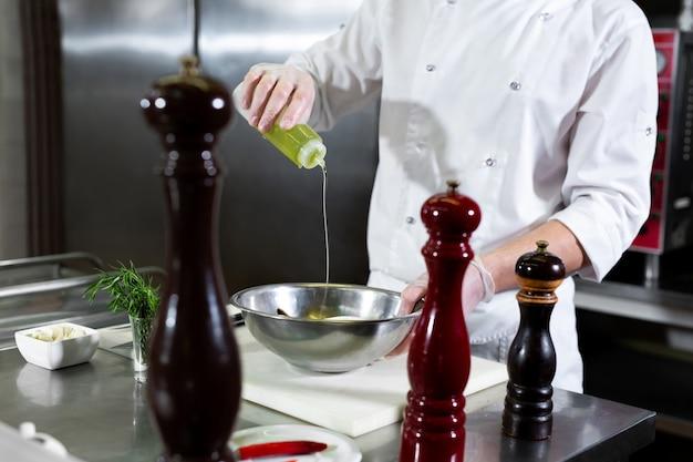 Chef-kok van het restaurant marineert zeevruchten in een kom
