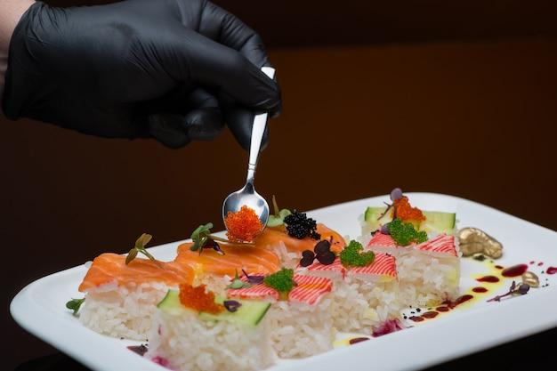 Chef-kok versiert sushi met kaviaar. proces van het koken van sushi