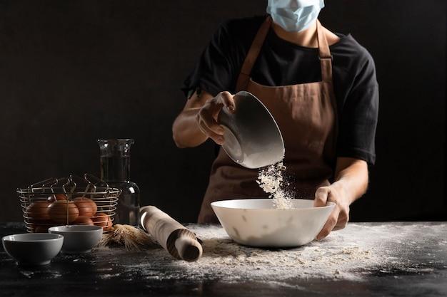 Chef-kok voegt bloem toe aan de kom om deeg te maken
