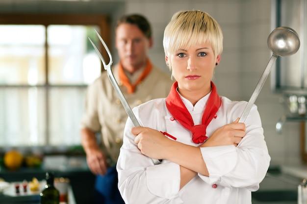 Chef-kok - vrouw - in restaurantkeuken het stellen