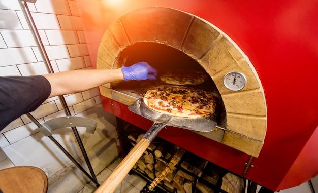 Chef-kok zet rauwe pizza in de oven