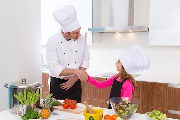 Chef-kokmeester en ondergeschikte het meisjeshanddruk van het leerlingsjonge geitje