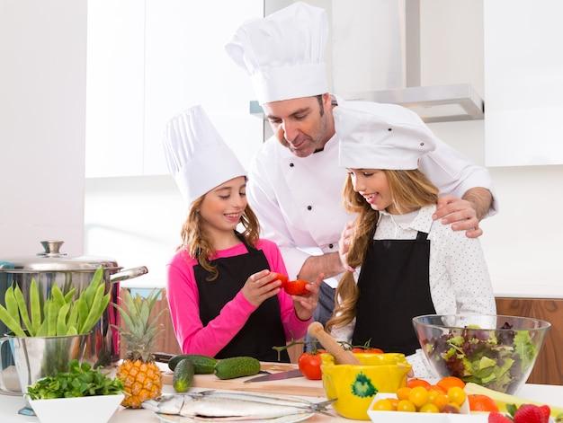 Chef-kokmeester en ondergeschikte meisjes van het leerlingsjonge geitje bij het koken van school