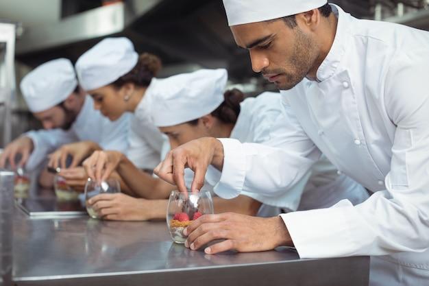 Chef-koks afwerking dessert in glas bij restaurant