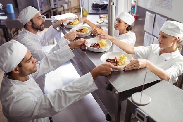 Chef-koks die klaar eten doorgeven aan de ober op het bestelstation