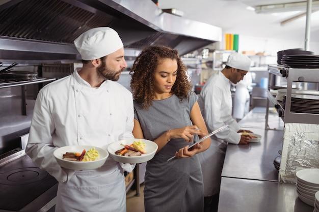 Chef-koks die menu op klembord bespreken