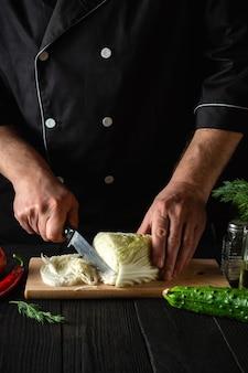 Chef-koks die verse chinese kool en groenten snijden voor salade