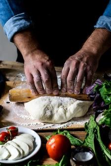 Chef-koks handen italiaanse chef-kok pizza koken man handen pizza deeg koken voor pizza