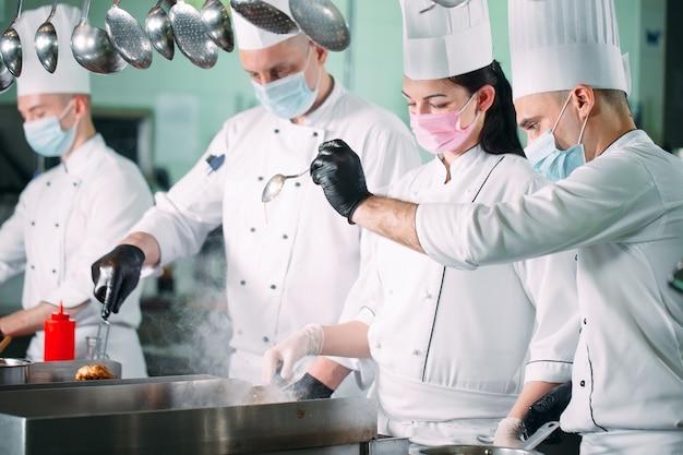 Chef-koks in beschermende maskers en handschoenen bereiden eten in de keuken van een restaurant of hotel.
