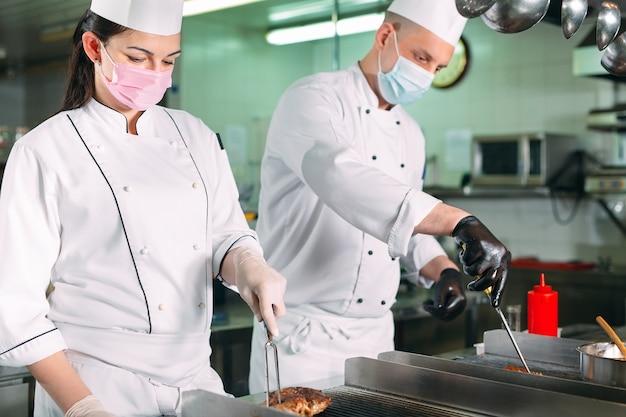 Chef-koks in beschermende maskers en handschoenen bereiden voedsel in de keuken van een restaurant of hotel.