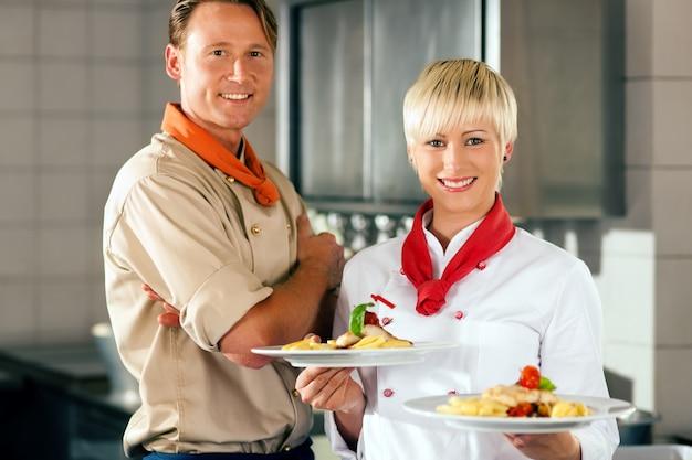 Chef-koks in een restaurant of hotel keuken poseren