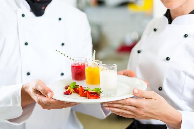 Chef-koksteam in restaurantkeuken met dessert