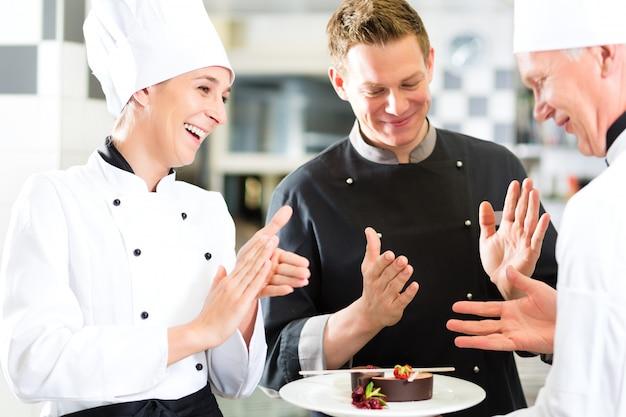Chef-kokteam in restaurantkeuken met dessert