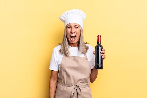 Chef-kokvrouw van middelbare leeftijd die agressief schreeuwt, erg boos, gefrustreerd, verontwaardigd of geïrriteerd kijkt, schreeuwend zonder een wijnfles vast te houden