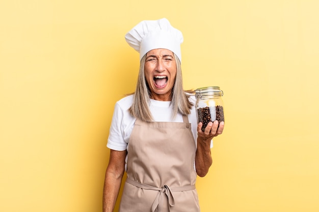 Chef-kokvrouw van middelbare leeftijd die agressief schreeuwt, erg boos, gefrustreerd, verontwaardigd of geïrriteerd kijkt, schreeuwend zonder koffiebonen vast te houden