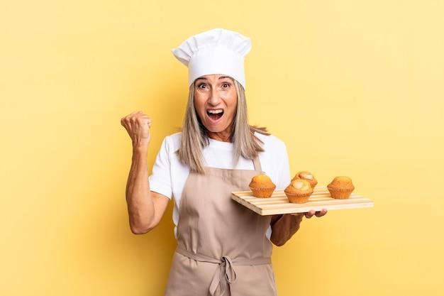 Chef-kokvrouw van middelbare leeftijd die agressief schreeuwt met een boze uitdrukking of met gebalde vuisten om succes te vieren en een dienblad met muffins vast te houden