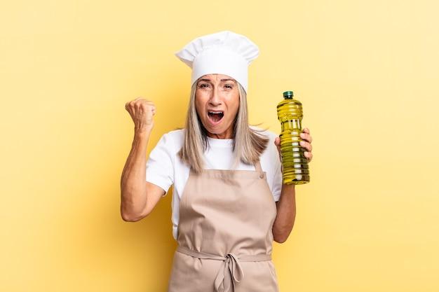 Chef-kokvrouw van middelbare leeftijd die agressief schreeuwt met een boze uitdrukking of met gebalde vuisten om succes te vieren