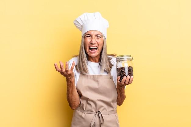 Chef-kokvrouw van middelbare leeftijd die boos, geïrriteerd en gefrustreerd kijkt, schreeuwend wtf of wat is er mis met jou die koffiebonen vasthoudt