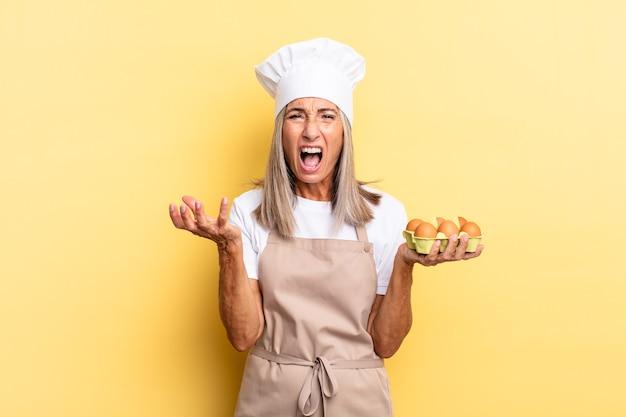 Chef-kokvrouw van middelbare leeftijd die boos, geïrriteerd en gefrustreerd schreeuwt wtf of wat is er mis met jou die een eierdoos vasthoudt