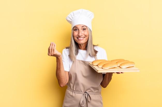 Chef-kokvrouw van middelbare leeftijd die capice of geldgebaar maakt en u vertelt uw schulden te betalen! en een broodblad vasthouden