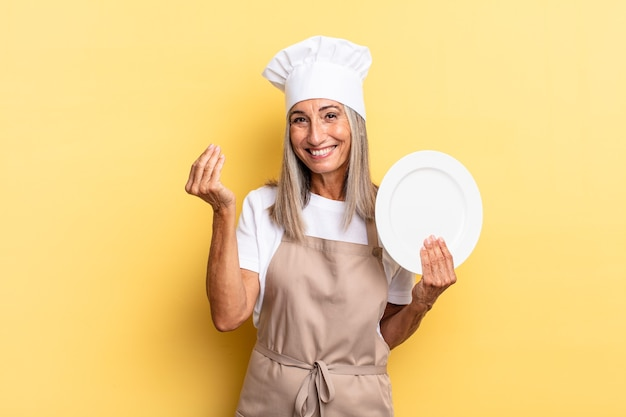 Chef-kokvrouw van middelbare leeftijd die capice of geldgebaar maakt en u vertelt uw schulden te betalen! en een schotel vasthouden