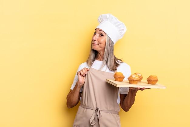 Chef-kokvrouw van middelbare leeftijd die er arrogant, succesvol, positief en trots uitziet, naar zichzelf wijst en een dienblad met muffins vasthoudt