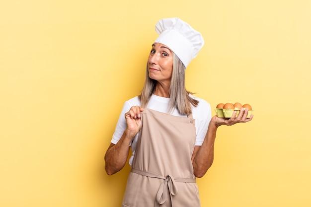 Chef-kokvrouw van middelbare leeftijd die er arrogant, succesvol, positief en trots uitziet, wijzend naar zichzelf met een eierdoos