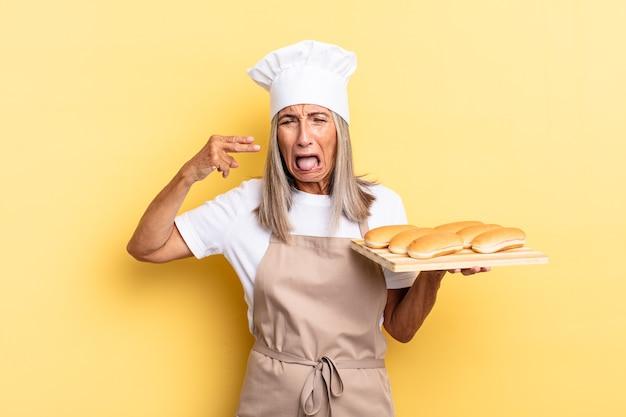 Chef-kokvrouw van middelbare leeftijd die er ongelukkig en gestrest uitziet, zelfmoordgebaar maakt een pistoolteken met de hand, wijst naar het hoofd en houdt een broodblad vast