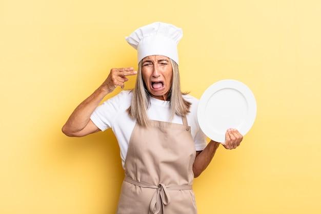 Chef-kokvrouw van middelbare leeftijd die er ongelukkig en gestrest uitziet, zelfmoordgebaar maakt een pistoolteken met de hand, wijst naar het hoofd en houdt een schotel vast