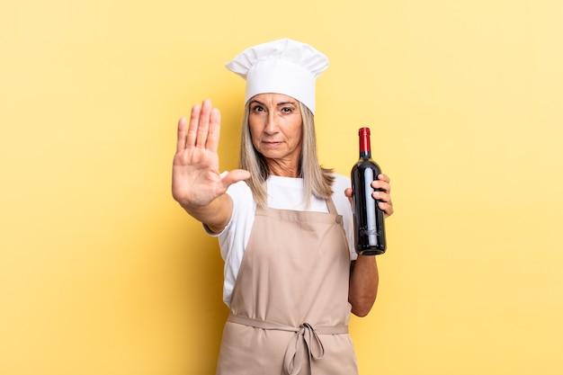 Chef-kokvrouw van middelbare leeftijd die er serieus, streng, ontevreden en boos uitziet met een open palm die een stopgebaar maakt met een wijnfles
