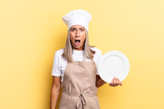 Chef-kokvrouw van middelbare leeftijd die erg geschokt of verrast kijkt, met open mond starend wauw zegt en een gerecht vasthoudt