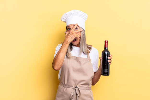 Chef-kokvrouw van middelbare leeftijd die geschokt, bang of doodsbang kijkt, haar gezicht bedekt met de hand en tussen de vingers gluurt die een wijnfles vasthoudt