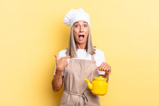Chef-kokvrouw van middelbare leeftijd die geschokt en verrast kijkt met de mond wijd open, naar zichzelf wijst en een theepot vasthoudt