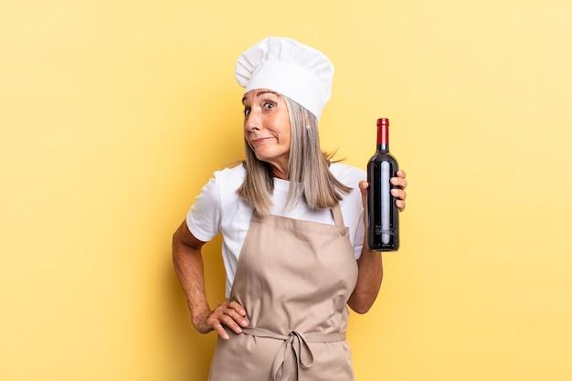 Chef-kokvrouw van middelbare leeftijd die haar schouders ophaalt, zich verward en onzeker voelt, twijfelt met gekruiste armen en een verbaasde blik met een wijnfles