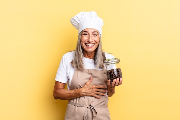 Chef-kokvrouw van middelbare leeftijd die hardop lacht om een hilarische grap, zich gelukkig en opgewekt voelt, plezier heeft met koffiebonen