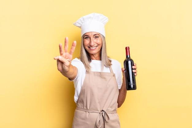 Chef-kokvrouw van middelbare leeftijd die lacht en er vriendelijk uitziet, nummer drie of derde toont met de hand naar voren, aftellend met een wijnfles
