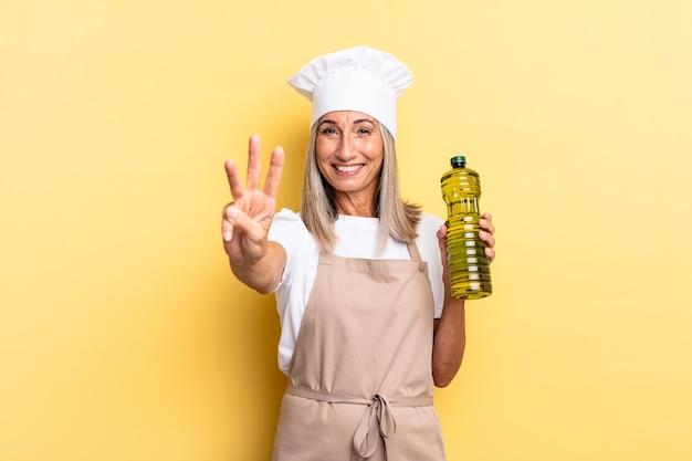 Chef-kokvrouw van middelbare leeftijd die lacht en er vriendelijk uitziet, nummer drie of derde toont met de hand naar voren, aftellend