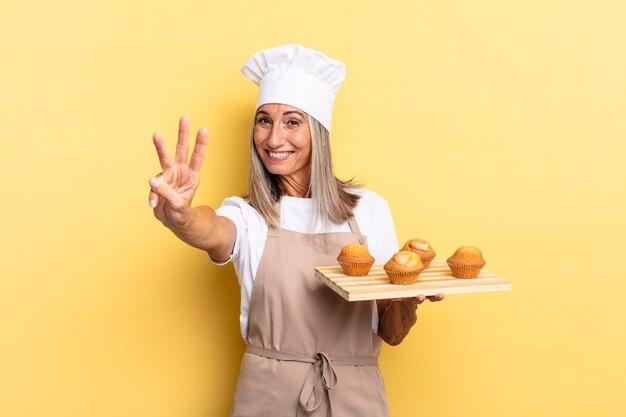 Chef-kokvrouw van middelbare leeftijd die lacht en er vriendelijk uitziet, nummer drie of derde toont met de hand naar voren, aftelt en een dienblad met muffins vasthoudt