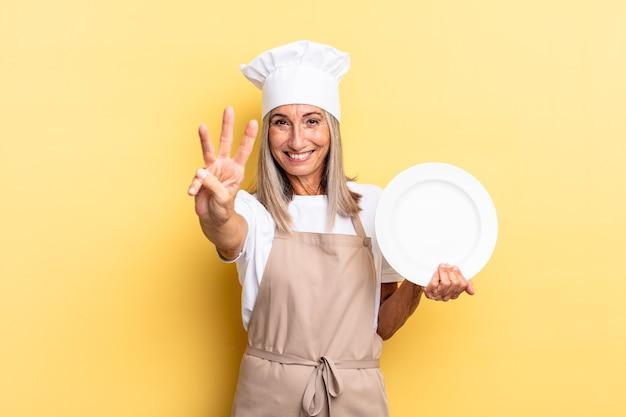 Chef-kokvrouw van middelbare leeftijd die lacht en er vriendelijk uitziet, nummer drie of derde toont met de hand naar voren, aftelt en een gerecht vasthoudt