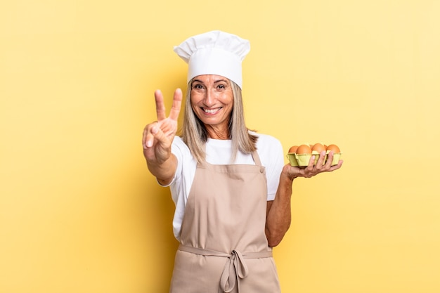Chef-kokvrouw van middelbare leeftijd die lacht en er vriendelijk uitziet, nummer twee of seconde toont met de hand naar voren, aftellend met een eierdoos