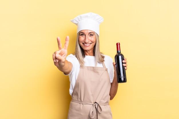 Chef-kokvrouw van middelbare leeftijd die lacht en er vriendelijk uitziet, nummer twee of seconde toont met de hand naar voren, aftellend met een wijnfles