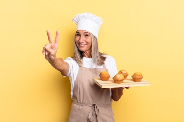 Chef-kokvrouw van middelbare leeftijd die lacht en er vriendelijk uitziet, nummer twee of seconde toont met de hand naar voren, aftelt en een muffinbak vasthoudt