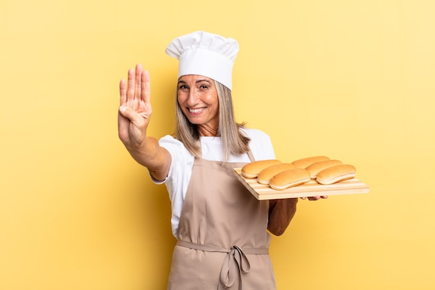 Chef-kokvrouw van middelbare leeftijd die lacht en er vriendelijk uitziet, nummer vier of vierde toont met de hand naar voren, aftelt en een broodblad vasthoudt