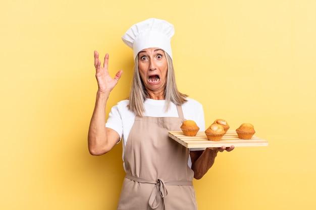 Chef-kokvrouw van middelbare leeftijd die met de handen in de lucht schreeuwt, zich woedend, gefrustreerd, gestrest en overstuur voelt en een dienblad met muffins vasthoudt