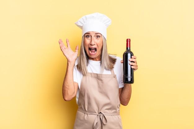 Chef-kokvrouw van middelbare leeftijd die met de handen in de lucht schreeuwt, zich woedend, gefrustreerd, gestrest en overstuur voelt terwijl ze een wijnfles vasthoudt