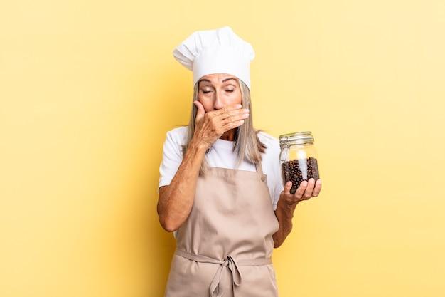 Chef-kokvrouw van middelbare leeftijd die mond bedekt met handen met een geschokte, verbaasde uitdrukking, een geheim houdt of oeps zegt met koffiebonen