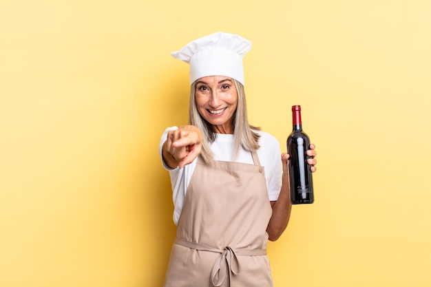 Chef-kokvrouw van middelbare leeftijd die naar de camera wijst met een tevreden, zelfverzekerde, vriendelijke glimlach, die ervoor kiest dat je een wijnfles vasthoudt