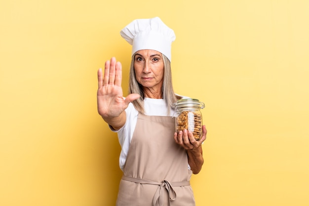 Chef-kokvrouw van middelbare leeftijd die serieus, streng, ontevreden en boos kijkt en een open palm laat zien die een stopgebaar maakt met koekjes