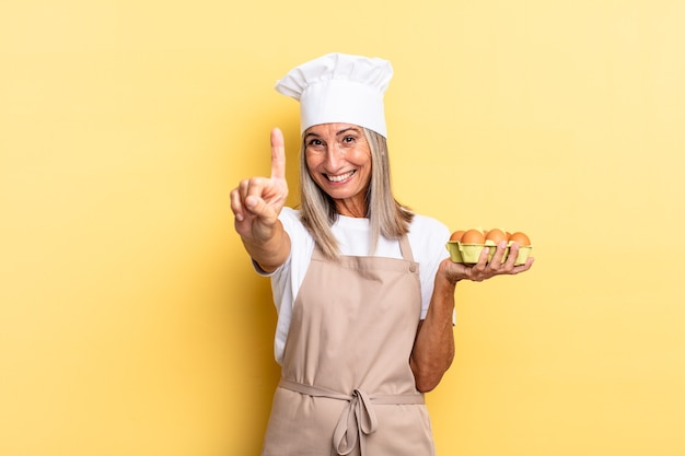 Chef-kokvrouw van middelbare leeftijd die trots en zelfverzekerd glimlacht en nummer één triomfantelijk poseert, voelt zich als een leider die een eierdoos vasthoudt